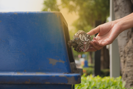 Female hand throwing crumpled paper into blue plastic trashcan. Stock Photo