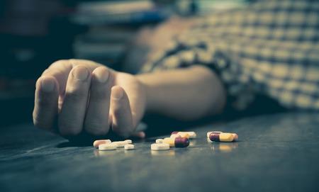 éxtasis: El hombre comete suicidio por sobredosis con medicamentos. Cerca de píldoras de sobredosis y adicto. Foto de archivo