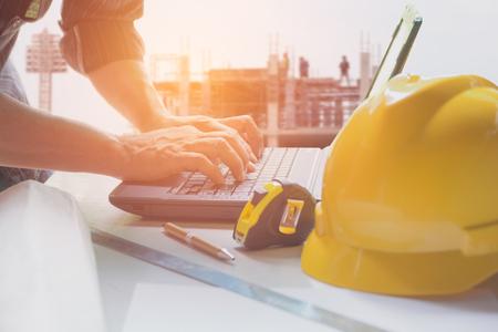 노란색 헬멧, 노트북 및 커피 컵 테이블에 작업을위한 랩톱을 사용하는 건축가 엔지니어.
