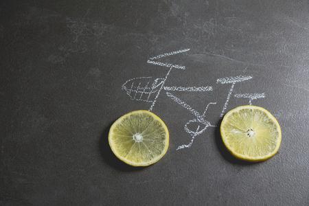 one wheel bike: lemon slice shape wheel of bicycle paint by chalk on black table background. Stock Photo
