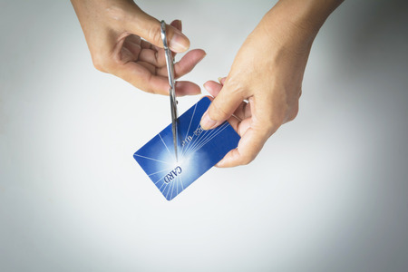 Cutting credit cards with scissors. Female hands cutting credit card with scissors.