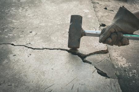 壊れたコンクリートを壊すためハンマーを使用している人。パワー、強さと破壊の概念。