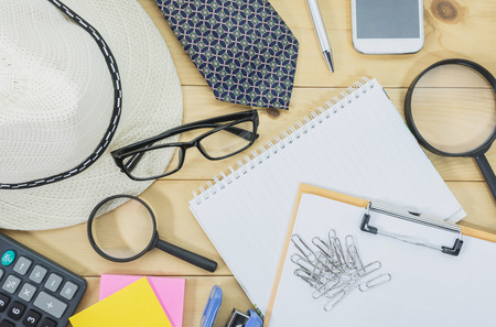 clutter: Office table top view with the glasses, note book, magnifying glass and mobile phone on desk cluttered. Cluttered office desk background.