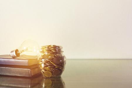 Sparende Glühlampe des Geldkonzeptes auf Büchern mit Geld im Flaschenglas, das für Geschäft Sepiaart wächst.