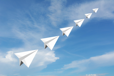 Paper airplane as a leader among another airplane , leadership, teamwork on blue sky background. Stock Photo