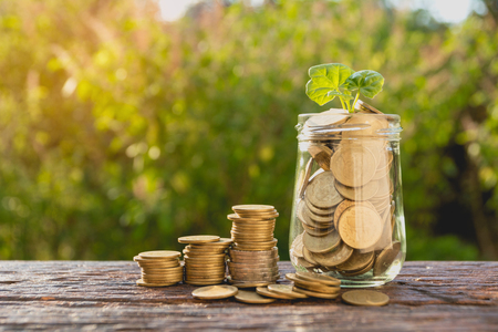 Coins in jar with money stack step growing money, Concept finance business and saving investment. 스톡 콘텐츠