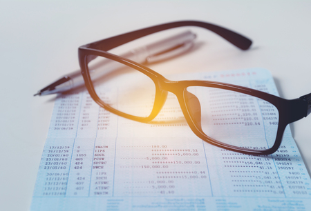Glasses with bank account passbook for savings financial and accounting concept.