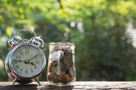 Coins in jar with alarm clock on nature background, Concept finance business, saving investment and accounting concept.