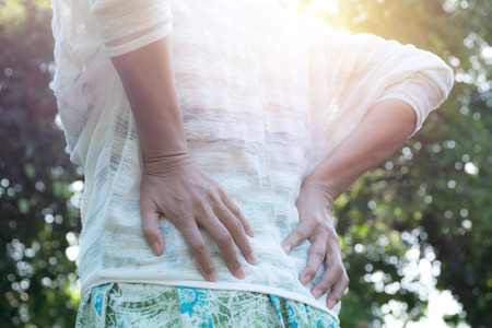 Woman with hands holding her waist back in pain. A woman pain concept.