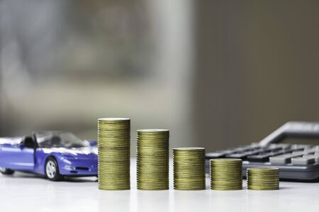 Car insurance and car service. Line graph with stack of coins and toy car, business and financial concept.