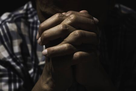 Hand of man while praying for religion. Concept peace and life.