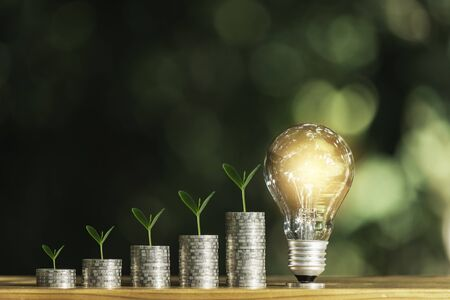 Light bulb with stack of coins and copy space for accounting, business and creative concept.