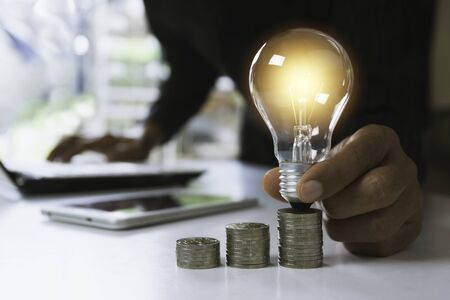 Hand of male holding a light bulb with stack of coins and copy space for accounting, ideas and creative concept. Stok Fotoğraf