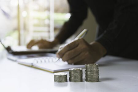 Person working and writing on notebook with stack of coins for financial and accounting concept. Stok Fotoğraf