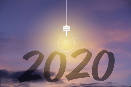 2020 Happy new year numbers with light bulb on sunset sky background