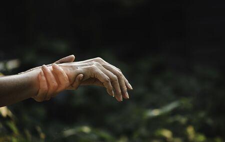 Female holding wrist. Pain in a woman wrist. Woman massaging painful wrist. pain concept. 스톡 콘텐츠