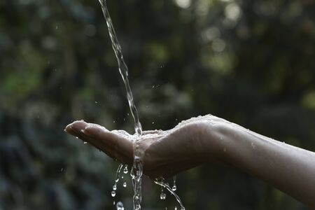 Water pouring on hand with blurred nature background. 스톡 콘텐츠