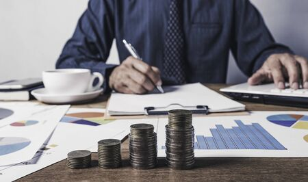 Business man working and writing on notebook with stack of coins for financial and accounting concept.