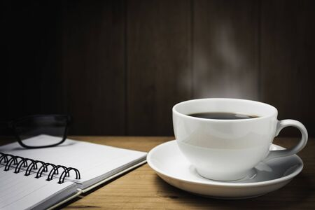 Wooden table desk with coffee. Workspace with note book, pen and coffee cup on wooden background with copy space. 版權商用圖片