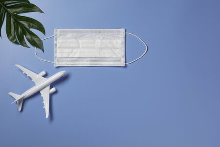 A toy airplane with medical mask for protecting virus and dust. Travel and protection concept.