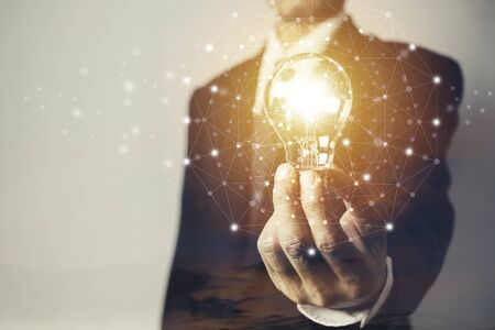 Business man holding a light bulb with sky and copy space for accounting, ideas and creative concept. Stock Photo