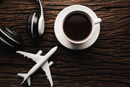 A cup of coffee with headphone on wooden table. Top view of coffee with copy space. Drink concept.