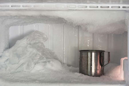 Stainless steel drinking water glass in freezer of a refrigerator. Ice buildup inside of a freezer walls. Imagens