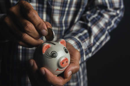 Saving money concept and hand putting money coin into piggy bank. Accounting and business concept.