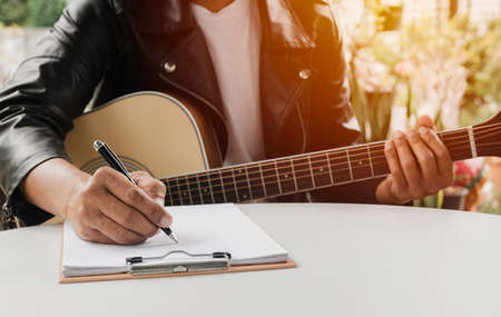 A Song writer holding pen for compose a song. Musician playing acoustic guitar. Live music and abstract musical concept. 스톡 콘텐츠