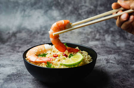 Hand using chopsticks pickup instant noodles on concrete background.
