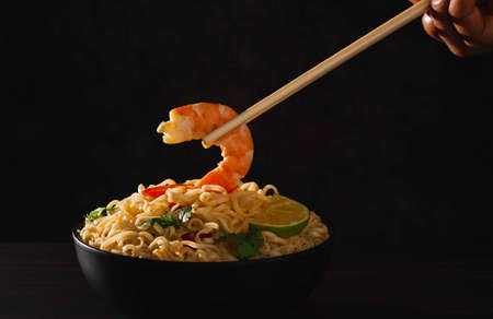Hand using chopsticks pickup instant noodles with smokes isolated on black background. 免版税图像