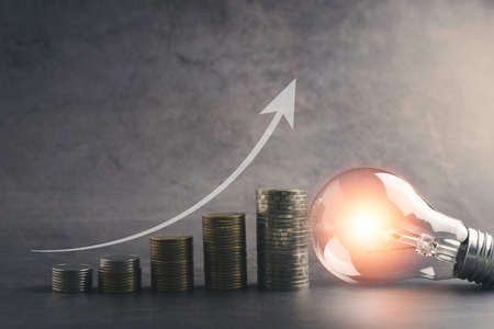 A light bulb with money coin stack growing for business. financial and accounting concept. 免版税图像