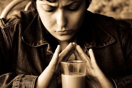 pesantezza: Profondamente pensando o preoccupata woman holding mani sul vetro pieni di met� del cacao. In color seppia.  Archivio Fotografico