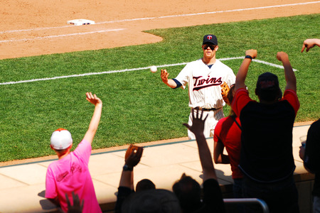 baseball dugout: A Minnesota Twins Player Tosses a Souvenier Baseball to a Young Fan at Target Field