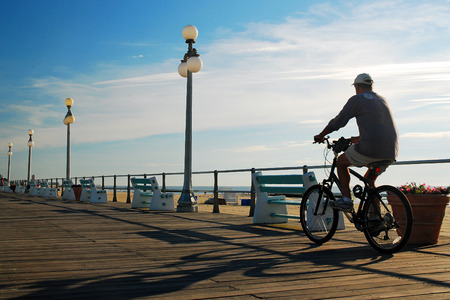 A Male Bicyclist Enjoys an Early Morning Ride on the Boardwalk in Avon on the New Jersey Shore