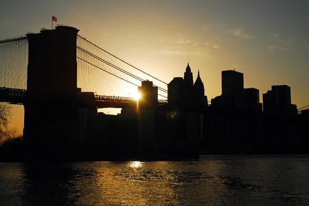 lower manhattan: The Sun Sets Behind the Brooklyn Bridge and Lower Manhattan Stock Photo