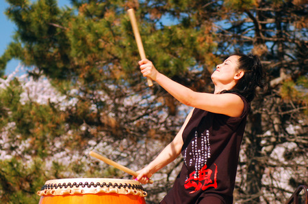 A Japanese Woman performs Traditional Taiko Drumming Stock Photo