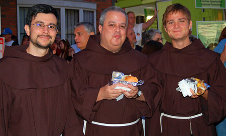 nosh: Three monks nosh on sausage and pepper hero at a festival in Bostons North End Editorial