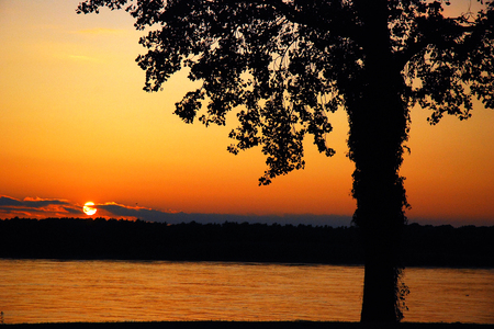 The sun sets on the Mississippi River, just north of Memphis Tennessee Stock Photo