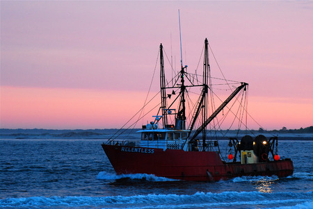 water alphabet: A fishing boat returns to port at dawn Editorial