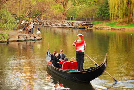 Couples enjoy a romantic gondola ride on a lake in New Yorks Central Park