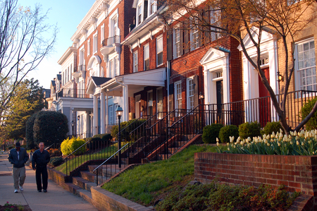 Two adult men walk past the historic homes on Monument Avenue in Richmond, Virginia