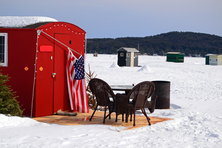 Patio furniture is set up in an unlikely location: outside of an ice fishing shack on Lake Winnipesaukee, New Hampshire