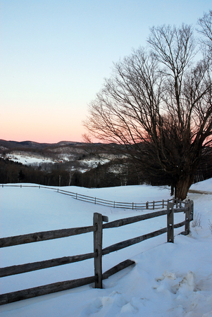 Dawn begins to shed light on a rural Vermont winter scene