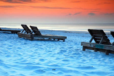 Wooden chairs await relaxers along the Gulf of Mexico Shore in Pensacola, Florida