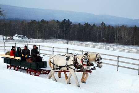 A horse drawn sleigh tours the country side during a snow fall Редакционное