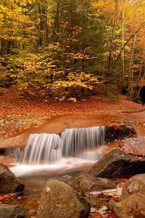 A waterfall surrounded by fall foliage Stock Photo