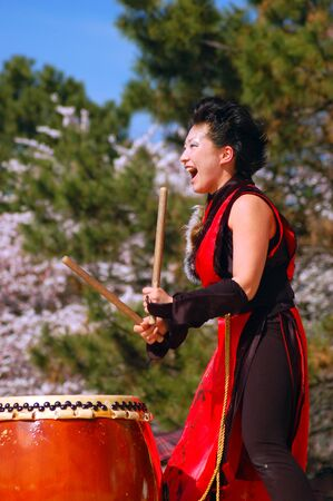 A young woman enthusiastically demonstrates the ancient art of Japanese Taiko drumming