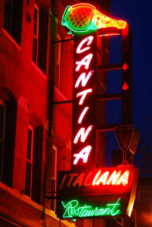 A large neon sign brightens a night scene in Boston's North End Editorial