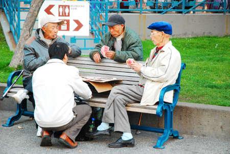 Elderly men enjoy a card game in Portsmouth Square, San Francisco